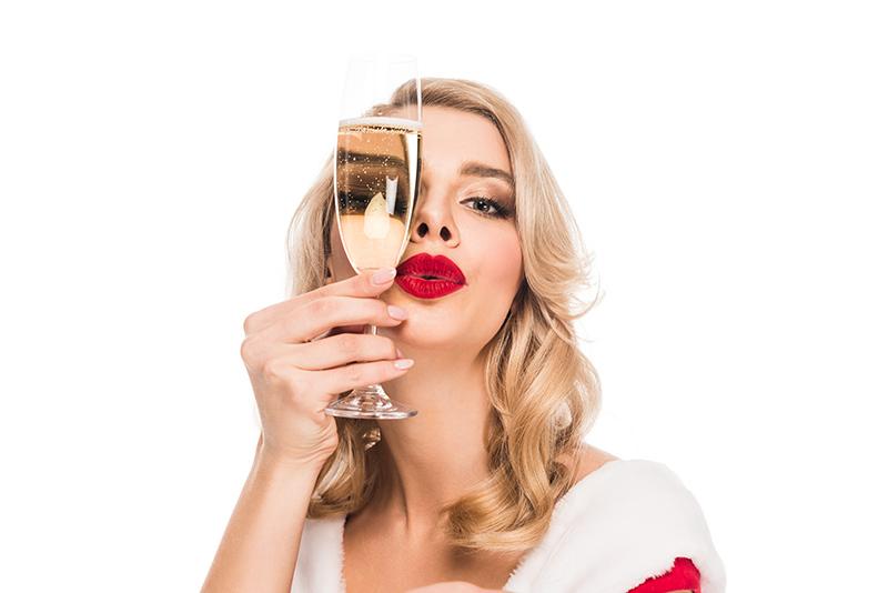 Sexy blonde Frau mit rotem Lippenstift und einem Champagnerglas vor der linken Gesichtshälfte
