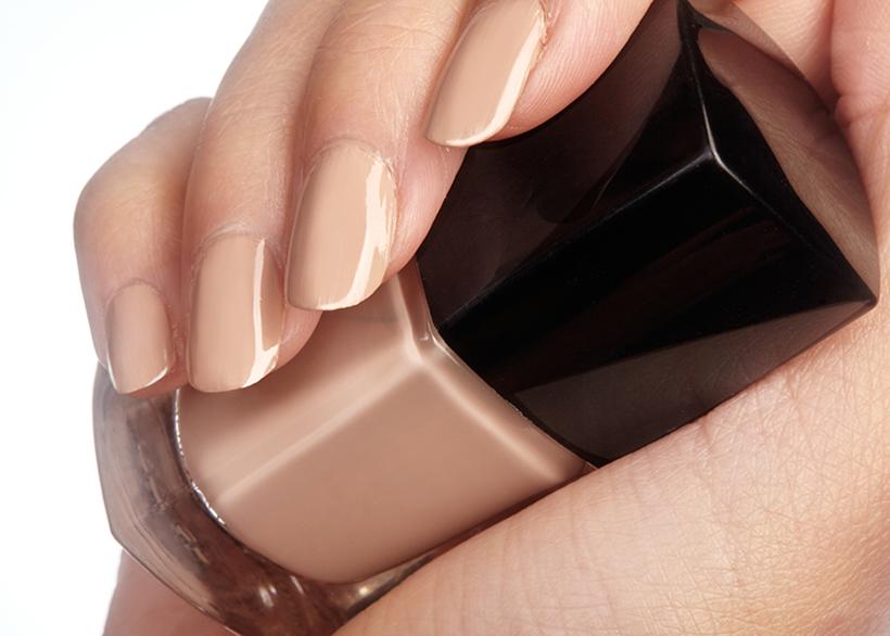 Hand mit nudefarbenen Nägel hält Nagellackflasche in der Hand
