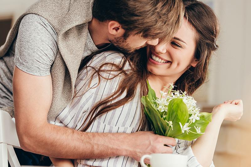 Mann umarmt Frau und schenkt ihr Blumen