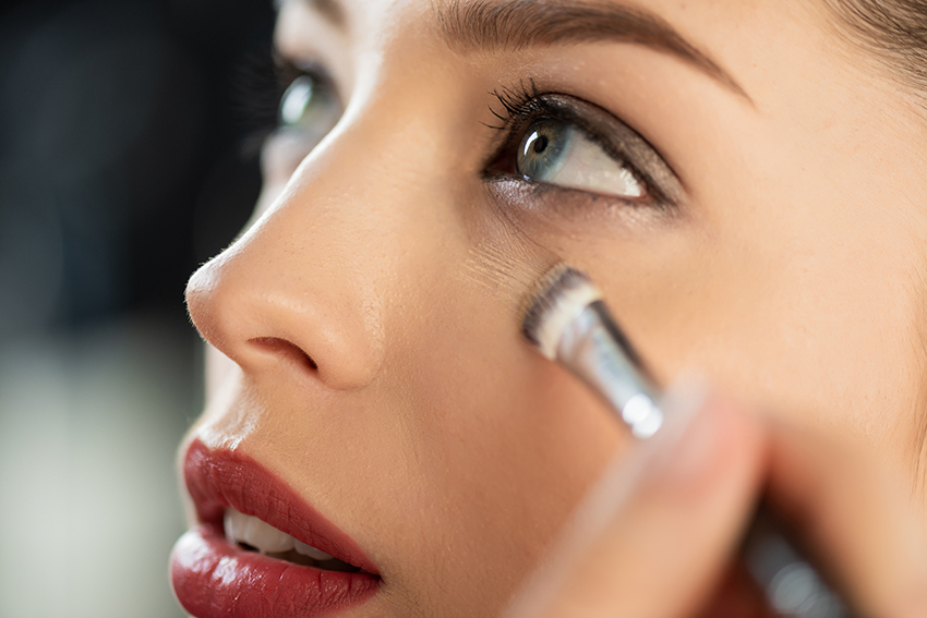 Frau die unter dem Auge geschminkt wird