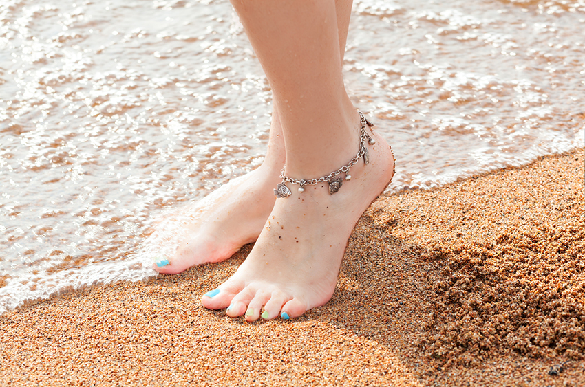 close-up of legs and a piece of jewelry for your feet. Young adult woman feet and toes, wearing anklet ankle bracelet resting in a summer vacation trip.