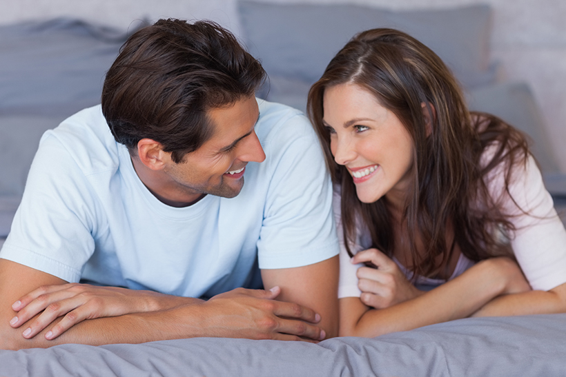 Man and woman lying on bed and looking at each other