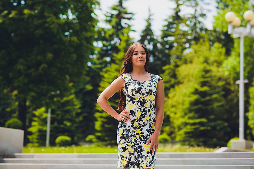 Portrait in full growth, young beautiful dark blonde woman in blue dress on street
