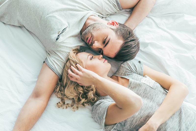 Ein Paar welches Kopf an Kopf auf einem Bett liegt und sich ansieht