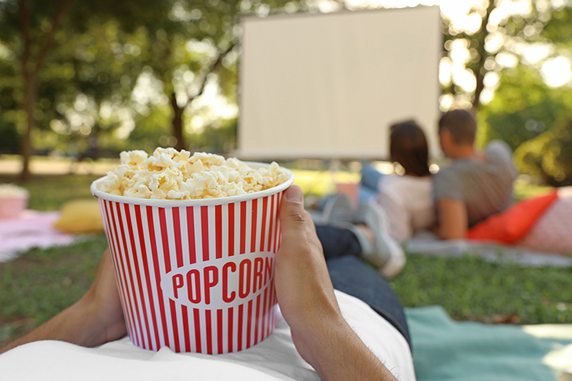 Young man with popcorn watching movie in open air cinema, closeu