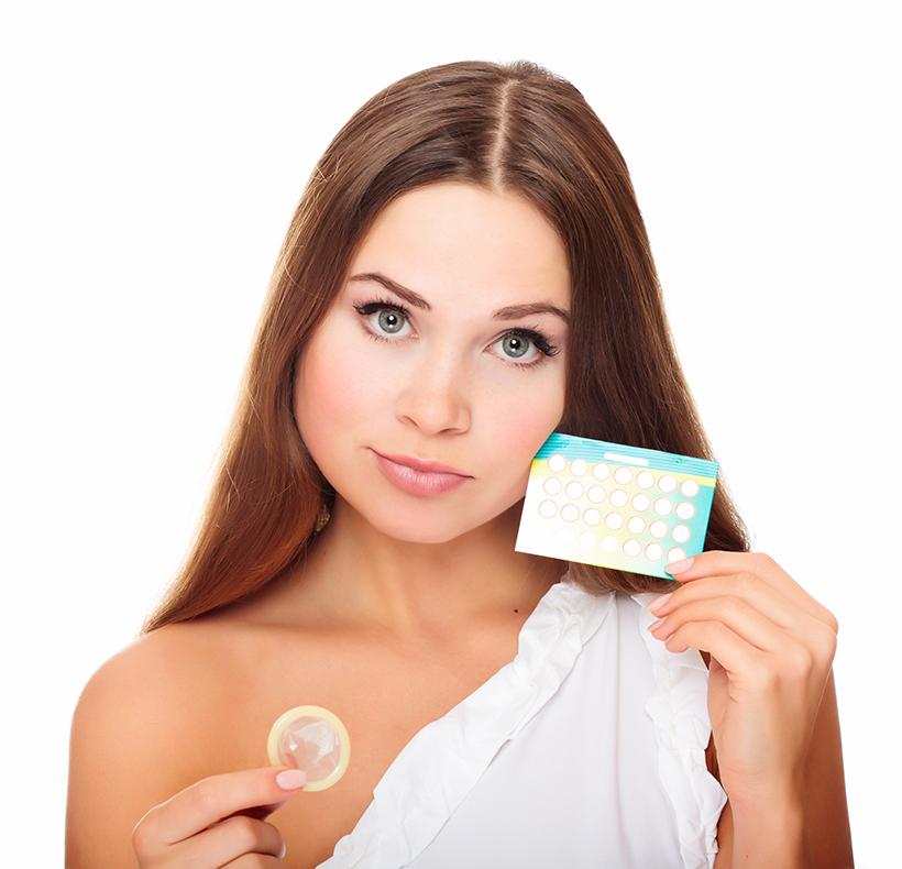 Pretty girl with condom and contraceptive pills